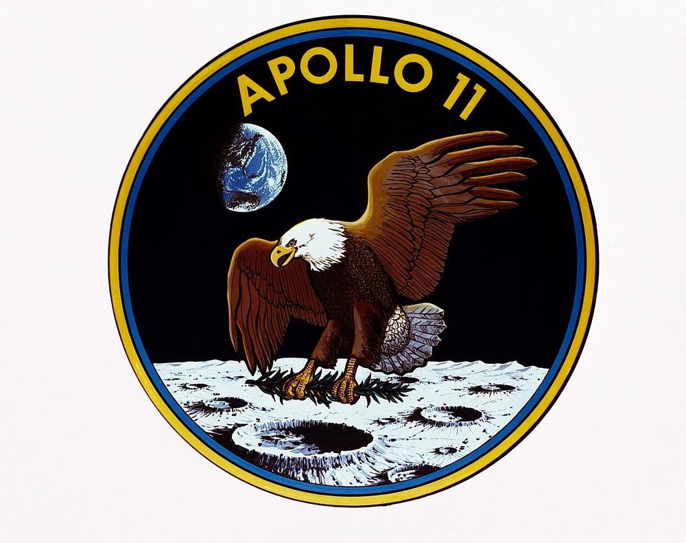 Az űrhajósoknak kellett a legénységi emblémát is megtervezni. Ez volt az Apollo-program legegyszerűbb logója (egy fehérfejű rétisas száll le a kráteres felszínű Holdon, karmai között – a béke jeleként – olajággal, háttérben a Földdel és az Apollo–11 felirattal).